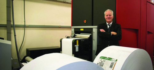 Compu-Mail Inc. President Michael L. Vitch stands with the company's Xeikon 9800.