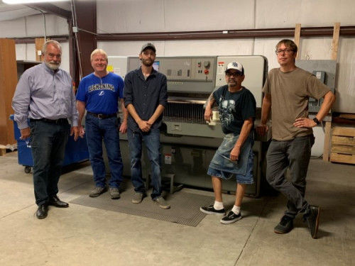 Standing with the Polar paper cutter are, from left to right: Rick Nesbit, Owner and Vice President; David Trimble, Facilities Manager; Production Operators Drew Parrish and Johnny Fernandez; and Terry Adams, Production Manager.