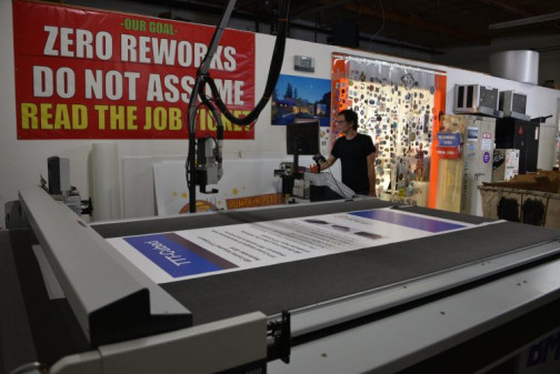 Matthew Tognetti, large-format operator, uses the Zünd cutter. Wide-format work has become a major market for PrintPapa.