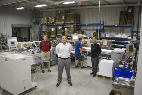Standing, from the left, are Chip Bell, VP of sales; Adam Monk, president; and Sheila Southall, VP of production. In the background, Danny Rhodes, bindery technician, operates a Heidelberg Stahl folder with Palamides delivery.
