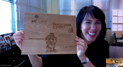 """Founder and CEO of PostcardMania, Joy Gendusa, proudly shows off her company's """"Really Gives a Sheet Award"""" plaque on a video call with Case Paper CMO, Simon Schaffer-Goldman."""