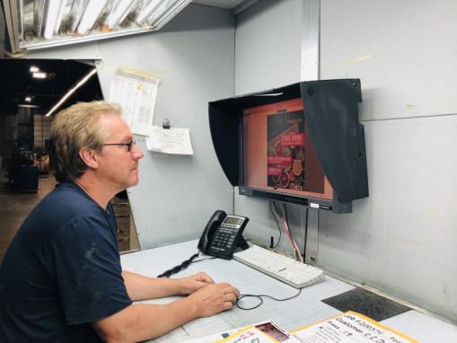 Larry Pacquer, Continental Web Press lead press operator, views the monitor to ensure color accuracy after a press gets to color.