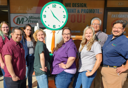 Minuteman Press franchise owner Peter Castorena (right) and his team in Lancaster, Calif., with their Giant Minute Man.