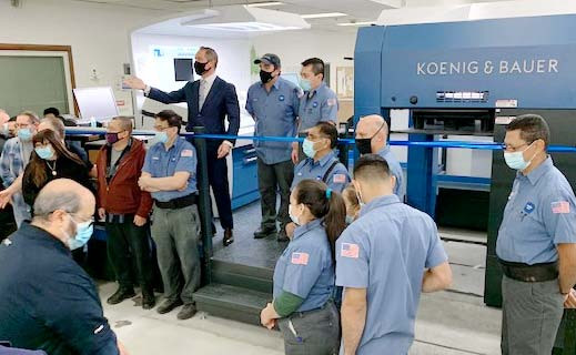 Mittera CEO Jon Troen (in suit and tie) gathered the press operators and New York employees to celebrate the ribbon cutting ceremony at the new Koenig & Bauer Rapida 105 PRO in December 2020.