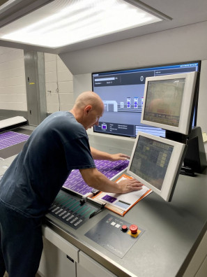 Allegheny's offset print operator, Jack Kelly, stands at the Komori press console.