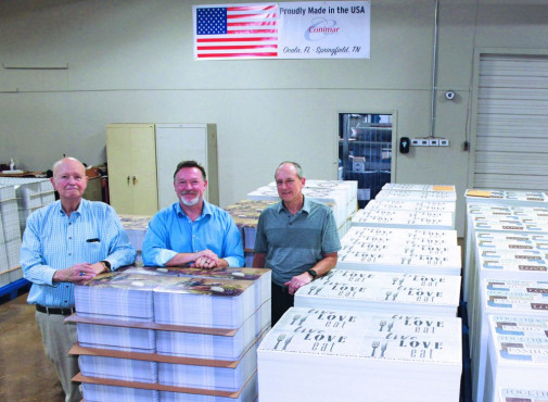 (Left to right) Conimar Group LLC, founder and CEO Terry Crawford; Conimar president Eric Robinson; and Conimar vice president of manufacturing Jim Mager; are surrounded by the firm's high quality placemats at the Ocala, FL facility where the new Koenig & Bauer Ipress 106 K PRO die cutter with blanker will arrive in early fall.