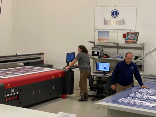 Matt Wagner, department lead, and Joe Dodson, plant manager, oversee work being produced on Linemark's EFI flatbed LED-UV printer and Kongsberg routing table.
