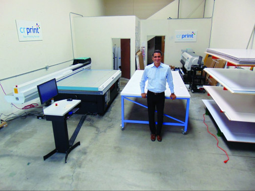 Mike Corridori, the owner of Westlake Village, Calif.-based CR Print, stands with his print shop's Fujifilm Acuity flatbed printer, which was installed just before the pandemic hit in February 2020.