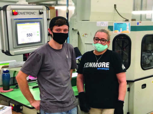 Standing in the Kenmore Envelope plant are Alec Ayers, adjuster, and Marisol Agosto, operator. The company takes pride that it didn't lay off or furlough any of its staff members due to the pandemic and, in actuality, hired more workers.