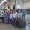 Marcus Wengerd (far right) poses with Carlisle employees in front of their 10-color Manroland LED-UV long perfector.