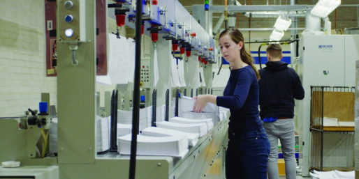 Anna Percival feeds book blocks on the Kolbus binder. With her is Jim Shorts.